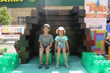 Two Siblings on top a blocky chair.